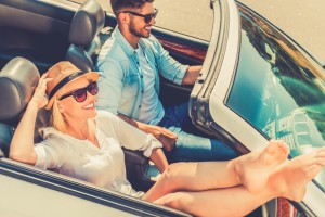 Weekend drive. Top view of smiling young woman relaxing while her boyfriend driving their convertible