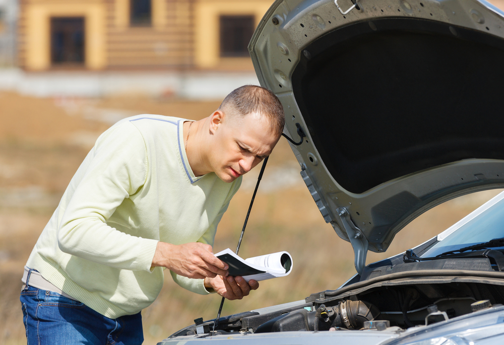 man broken down car reading user manual